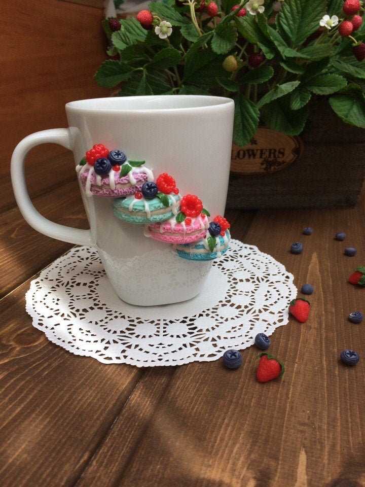 White cup for tea, Sweet mug and spoon decor, macaroons on a mug, delicious spoon with berries