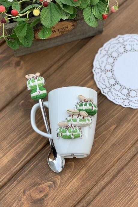 White cup for tea, Sweet mug and decor spoon, macaroons on the mug, delicious spoon with berries, green decor, sweet cookies.